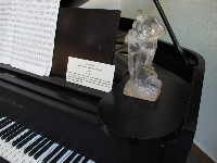 Eternal Moment figurine on a piano in Polasek's house, plus a piece of music that he wrote.