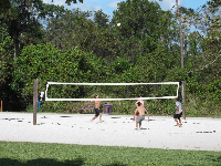 Guys playing sand volleyball.