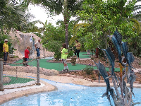 A family enjoys a Sunday morning game of mini golf.