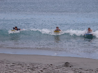 Kids bodyboard in to shore on an April day.
