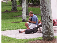 Happy guy playing guitar at Veterans Park.