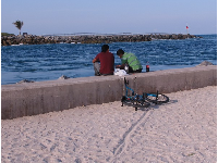 Two boys sit on the cement sea wall, bike in the sand.