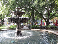 The Spanish fountain in the pretty area with large trees near Indigo Coffee.