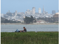 A couple relaxes while enjoying the view of the San Francisco skyline.