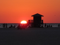 The sun falls behind the lifeguard shack as a couple watches from beach chairs.