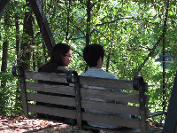 A couple chat on the swinging bench beside the lake.