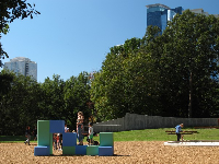 Giant blocks to climb at the Noguchi playground, with skyscrapers behind.