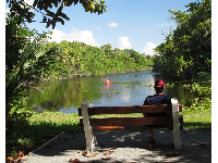 A man sits on a bench while a lady paddles a kayak.