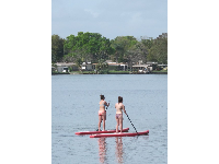 Two young women paddle on the lake.