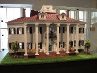 Colonial doll house with white columns.