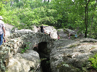Visitors walk over a stone bridge.