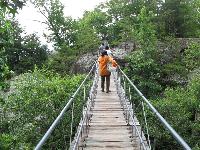 Visitors make their way across the swinging bridge.