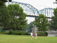 College students play catch on the lawn with views of the bridge behind.