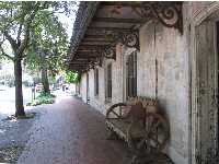 Historic building with curlicues, and rugged wooden bench.