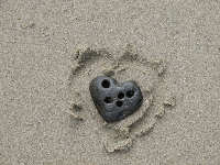 Heart-shaped rock in the sand.