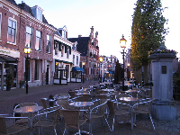 Outdoor brasserie seating by the old church, at night.