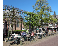 People enjoy a warm spring day outside the brasserie.
