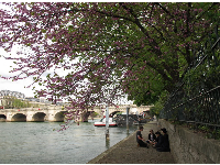 A group of young people hang out, with views of Pont Neuf behind them.