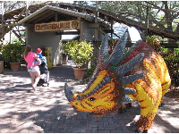 A lego dinosaur in front of Coastersaurus.