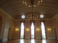 The ballroom with its high ceiling and elegant curtains.