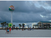 Flying a kite, with the giant beach ball in the distance.