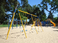Colorful playground with sandy floor.