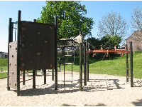 Play structure with rope ladder, monkey bars, and two rock climbing mini-walls.