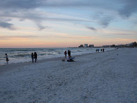 People gather on a cold evening at the shore.