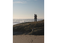 A loving couple stand and listen to the sea.