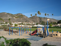 Spyglass Playground, backed by hills and palms.