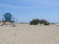 The pale blue lifeguard shack at the southernmost part of the beach.