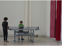 Kids playing ping pong on the third level balcony.