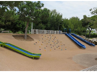 The playground with roller slide, two slides going down the hill, and rock climbing grips on the hill.