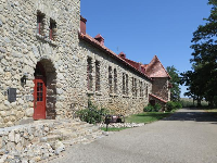 The long, stone building with a red door.