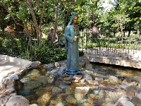 Statue of a nun by the stream.