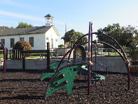 The playground and little schoolhouse behind.