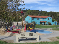 Couple sitting at the pirate playground. Central Coast Aquarium and the wonderful hills and forest behind.