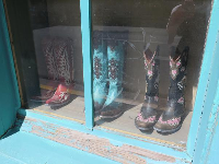 Boots for sale in a turquoise window.
