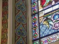 Closeup of stained glass and painted wall.