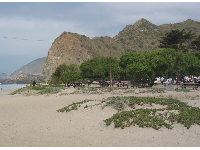 View of popular shady picnic area and barren mountains, as seen from the only secluded picnic area on the left side of the beach.