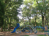 The space age playground in the shade of many trees.