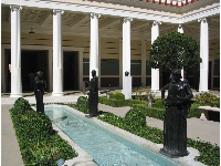 Black sculptures against white columns, and a pool, in the middle courtyard.