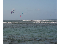 The multi-colored view of five kitesurfers.