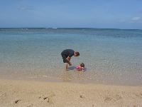 A father and baby girl in the calm waters close to shore.