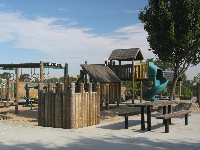 The wooden playground, with shade-giving roofs, twisty slide, and monkey bars.