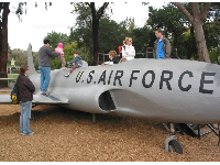Kids sit in the cockpit and climb on the wings of the fighter plane at Oak Meadow Park.