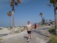 A man jogs from Ocean Blvd down the promenade between the hotel and the sand.