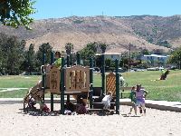 The toddler playground with yellow hills behind.