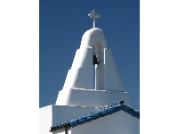 White bell tower, blue tile roof, and blue sky.