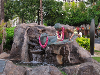 Cute statue of a Hawaiian monk seal and surfer.